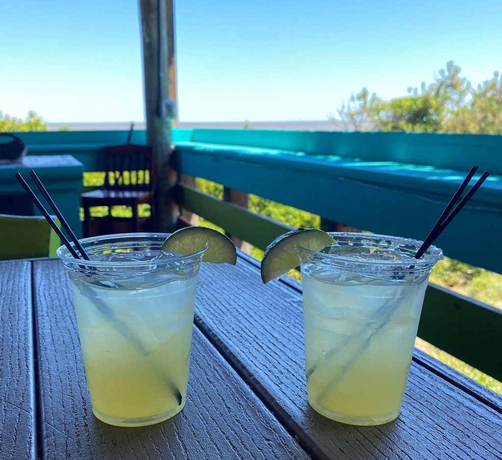 Two cups of margarita on the rocks from Tortuga Jacks, overlooking an ocean view