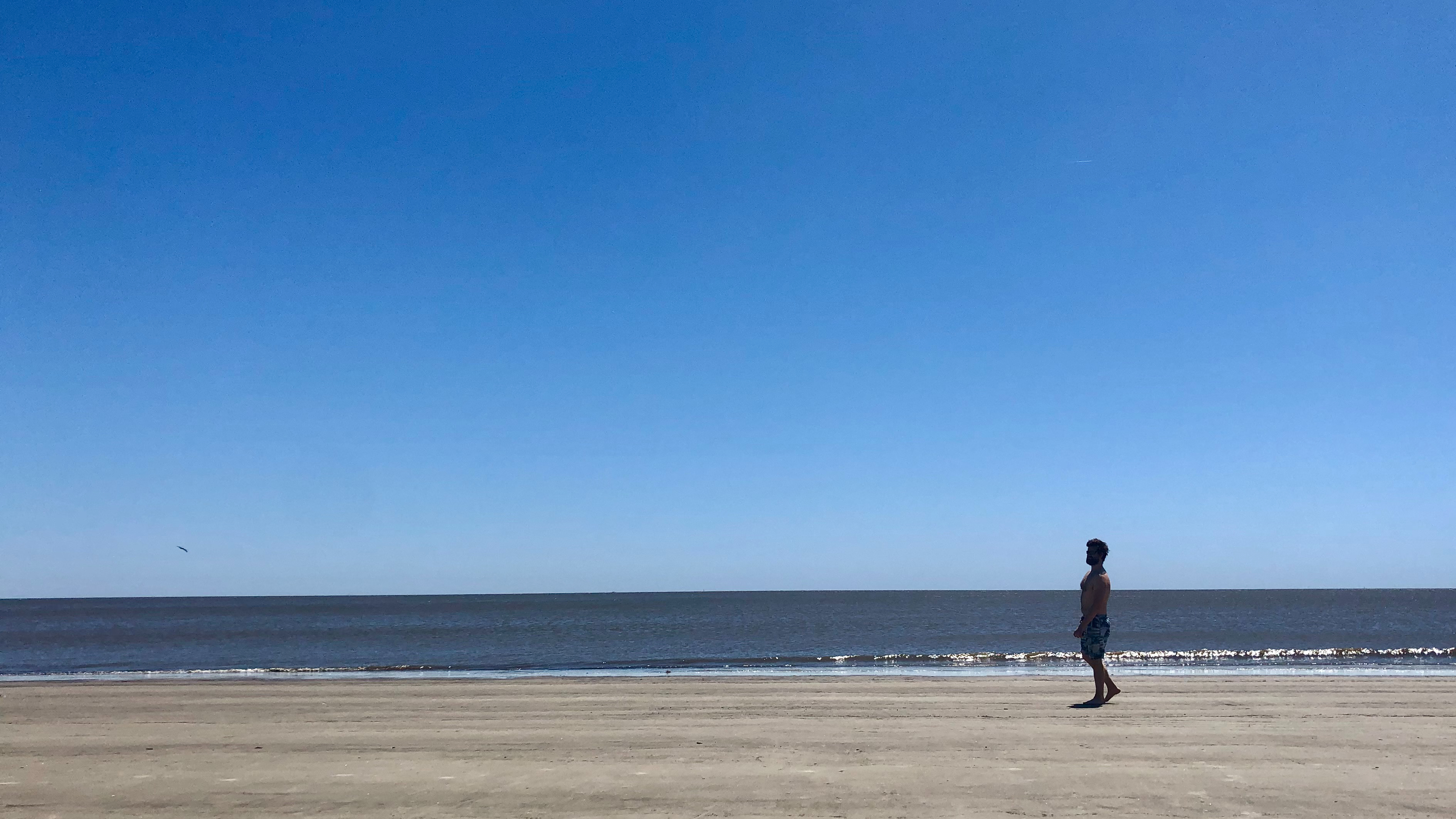 Man walks alone in the beach during a beautiful day without any clouds in the blue sky